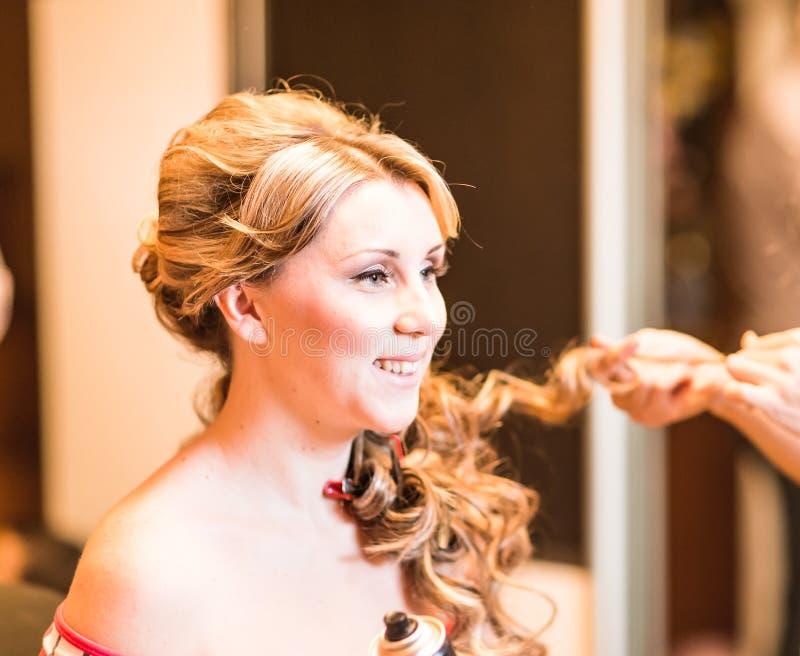 Le coiffeur fait une coiffure à la jeune mariée images libres de droits