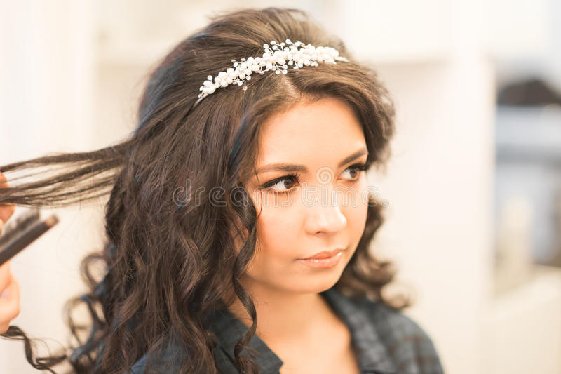 Le coiffeur fait une coiffure à la jeune mariée image stock