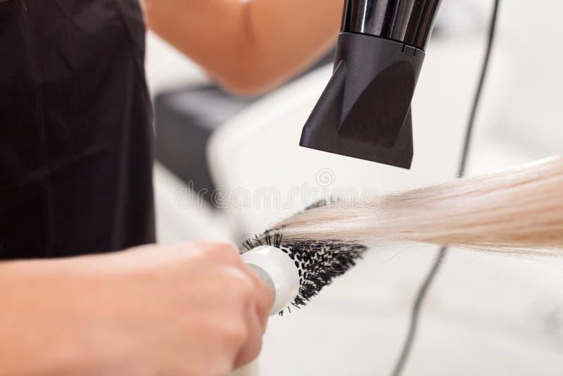 Le coiffeur gai sert le client à la beauté photo libre de droits