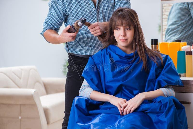 Le coiffeur masculin d'homme faisant la coupe de cheveux pour la femme images libres de droits