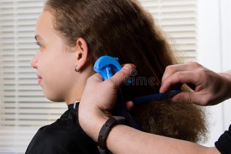 Le coiffeur peigne l'enfant, avec les cheveux bouclés et hydrate les cheveux avec un pulvérisateur photographie stock libre de droits