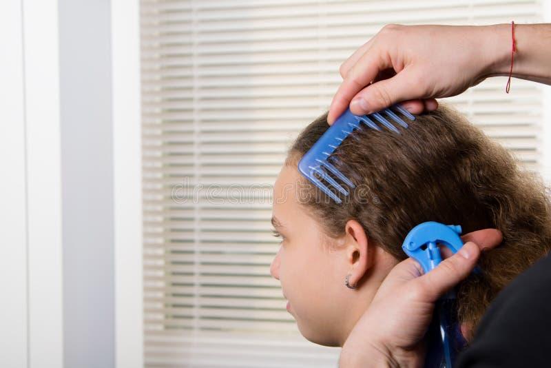 Le coiffeur peigne l'enfant et hydrate les cheveux avec un pulvérisateur de l'eau photos stock