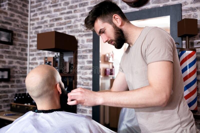 Le coiffeur principal professionnel coupe la barbe de client image libre de droits