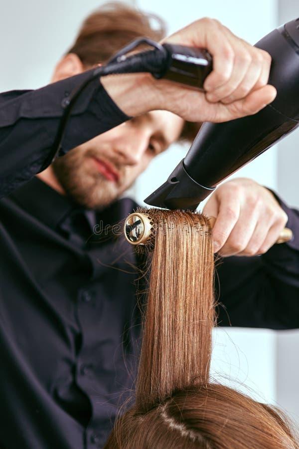 Le coiffeur sèche les cheveux avec le sèche-cheveux de la jeune, belle fille dans un salon de beauté photos libres de droits