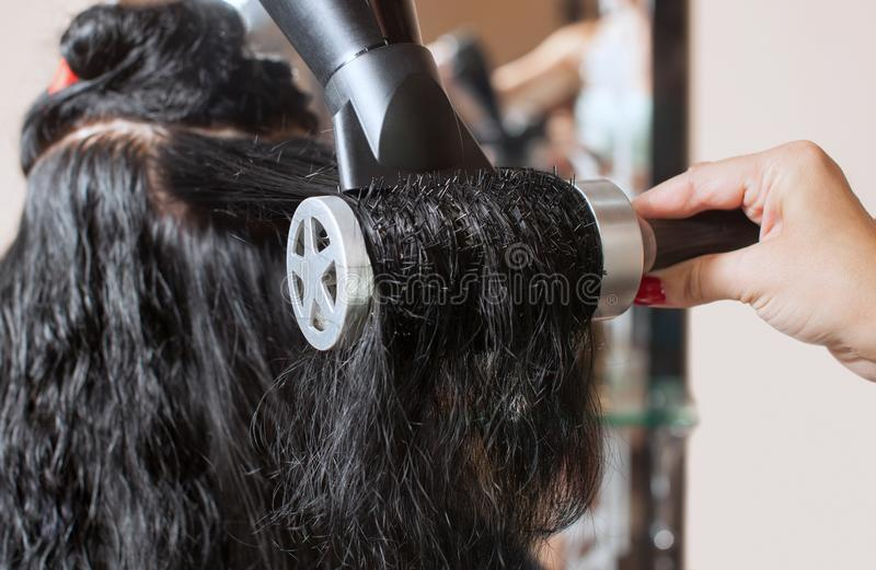 Le coiffeur sèche ses cheveux une fille de brune dans un salon de beauté images libres de droits