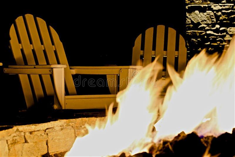 Le coin du feu Adirondack préside le puits du feu photo stock