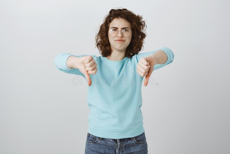 Le collègue pense que l'idée suce Portrait de jeune femme européenne déçue contrariée en verres, montrant des pouces vers le bas images stock