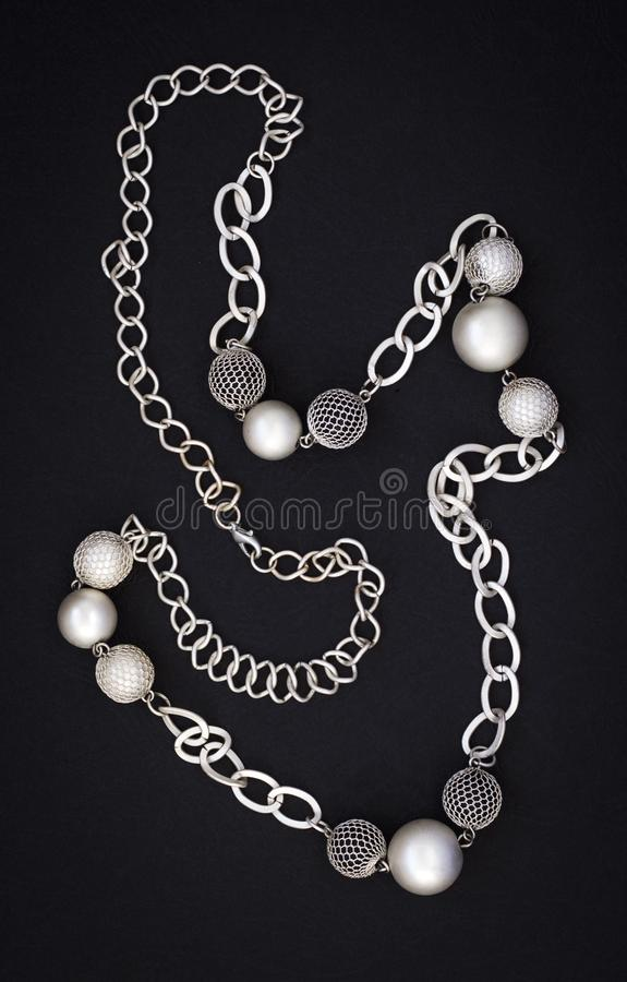 Le collier abstrait moderne des femmes sous forme de chaîne et les boules sur un fond noir photographie stock libre de droits