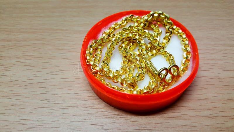 Le collier d'or est placé dans une boîte en plastique rouge sur la table en bois photo libre de droits