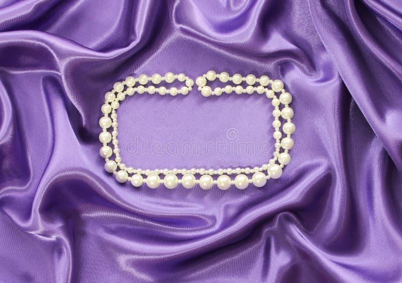 Le collier de perle sur la soie bleue drapent photos libres de droits