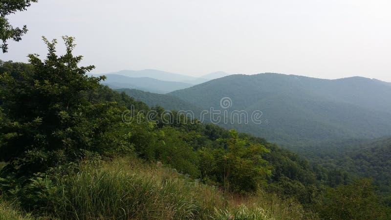 Le colline delle montagne di Ridge blu lungo orizzonte guidano fotografia stock