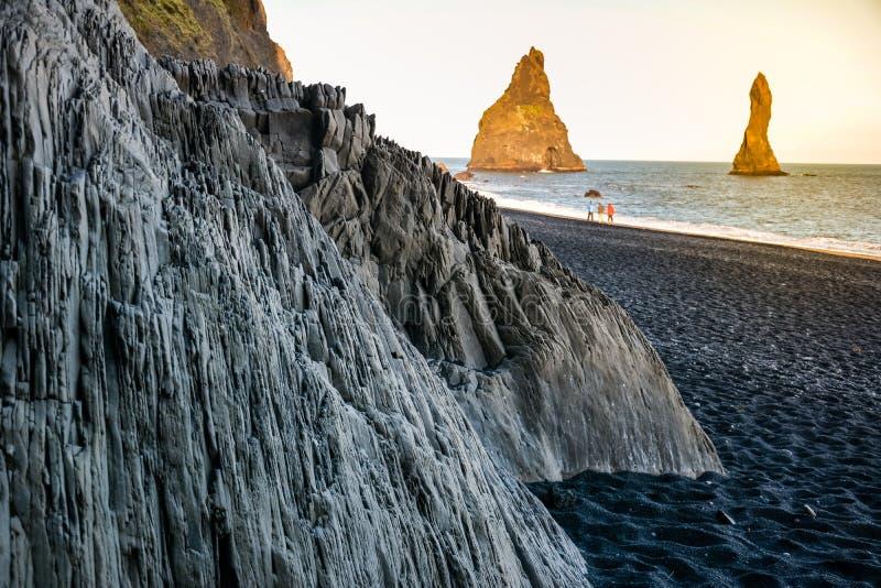 Le colonne di pietra del basalto su Reynisfjara anneriscono la spiaggia vicino alla città di Vik fotografia stock