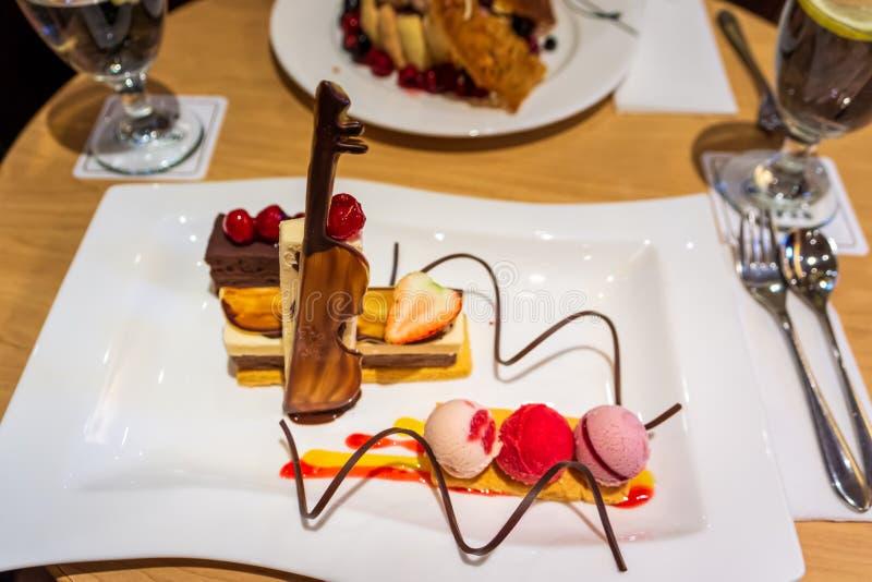 Le coloré délicieux crème avec la fraise et les cerises fraîches, le violon de chocolat et les spirales images stock