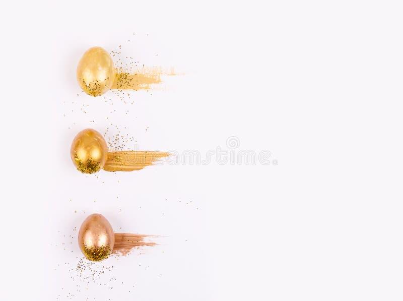 Le colore trois d'or a peint des oeufs images libres de droits