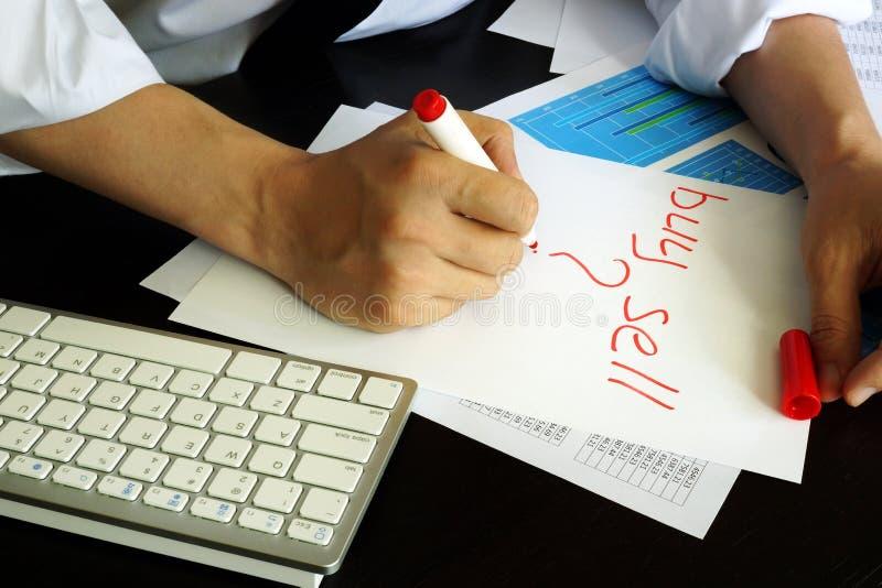 Le commerçant écrit l'achat ou la vente dans une note photo libre de droits