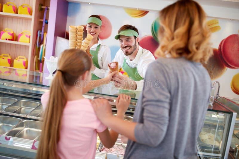 Le commerçant dans la boutique de pâtisserie donne la crème glacée à la fille photographie stock libre de droits