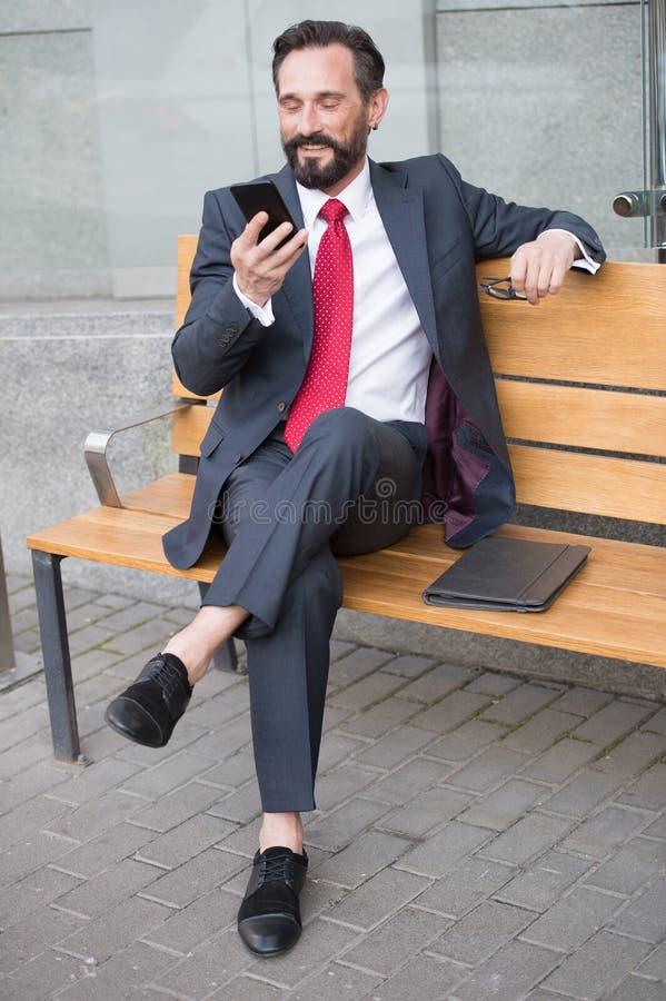Le commerçant s'asseyant sur le banc et font l'affaire Homme d'affaires utilisant la technologie du sans fil contrôlant des proce image stock