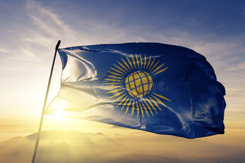 Le Commonwealth des nations marquent le tissu de tissu de textile ondulant sur le brouillard supérieur de brume de lever de solei illustration de vecteur