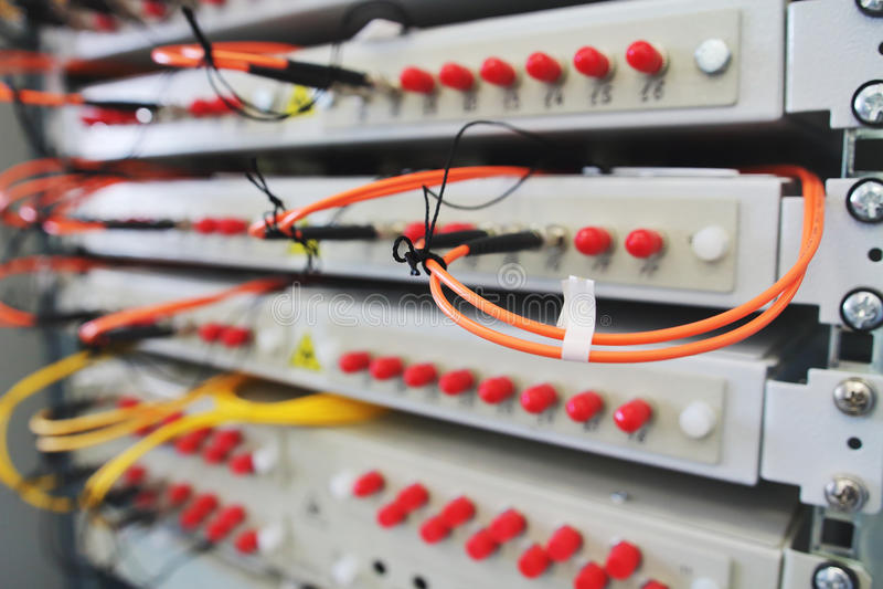 Le commutateur de réseau sur le support avec des câbles s'est relié dans la chambre de centre de traitement des données image stock