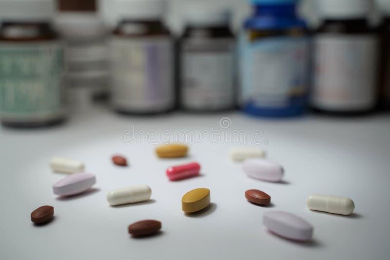 Le compresse e le pillole della capsula pongono davanti alle bottiglie confuse su fondo bianco fotografia stock libera da diritti