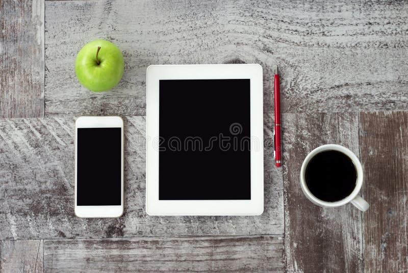 Le comprimé blanc, le téléphone, la tasse de café, le stylo et la pomme verte sont sur la table Travail ? la maison ind?pendant image stock