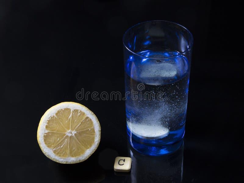 Le comprimé de vitamine C bouillonne en verre de l'eau et de citron photo stock