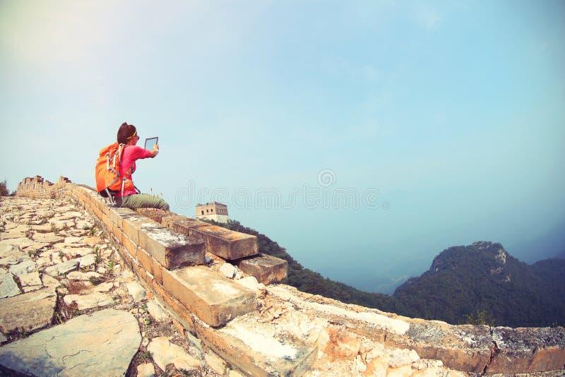 Le comprimé numérique d'utilisation de randonneur de femme se reposent sur la Grande Muraille chinoise photo libre de droits