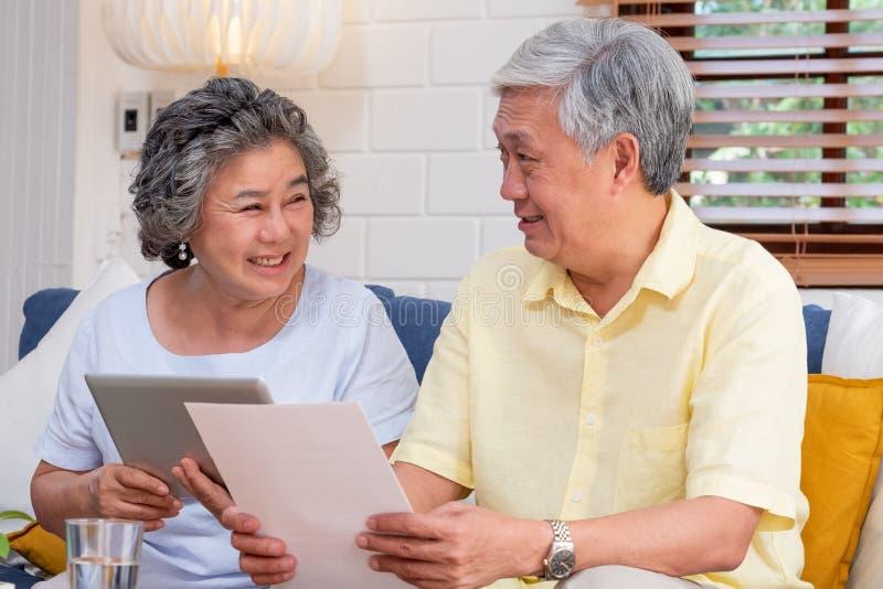 Le comprim? sup?rieur asiatique d'utilisation de couples recherchant au sujet du document financier de retraite se reposant sur l photographie stock libre de droits