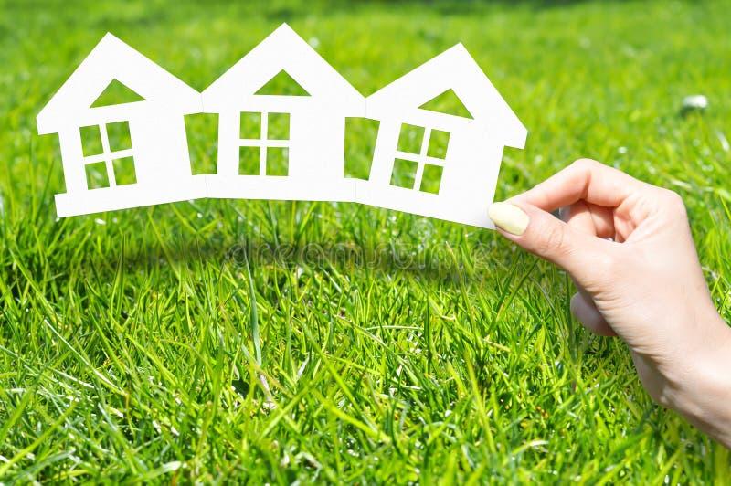 Le concept à la maison d'assurance avec la main tenant la maison a formé des documents imprimés sur l'herbe verte image stock