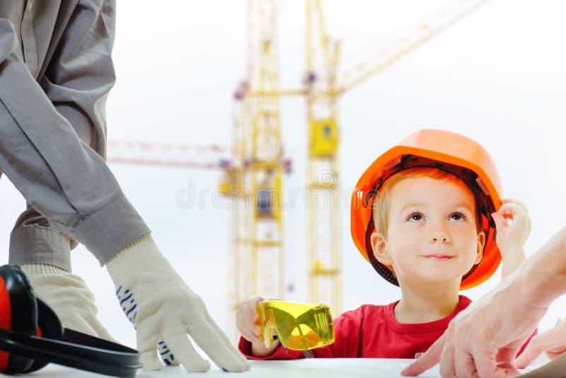 Le concept, constructeurs discutent avec l'enfant au-dessus du dessin Site de ville de construction d'équipement de protection de images libres de droits