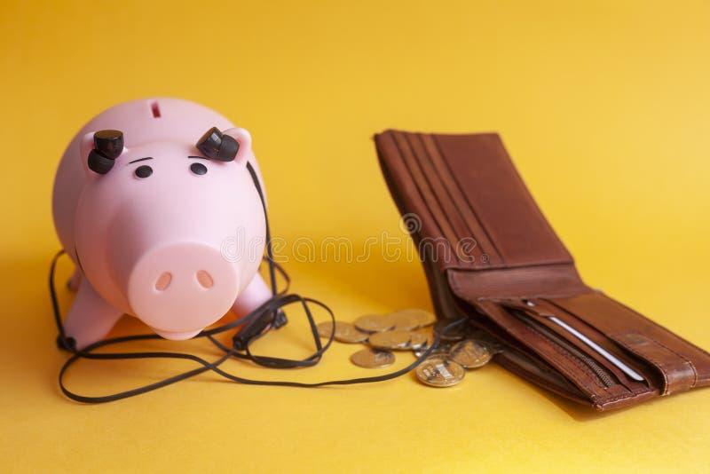 Le concept d'écouter le marché monétaire, tirelire avec des écouteurs écoutent un portefeuille image libre de droits