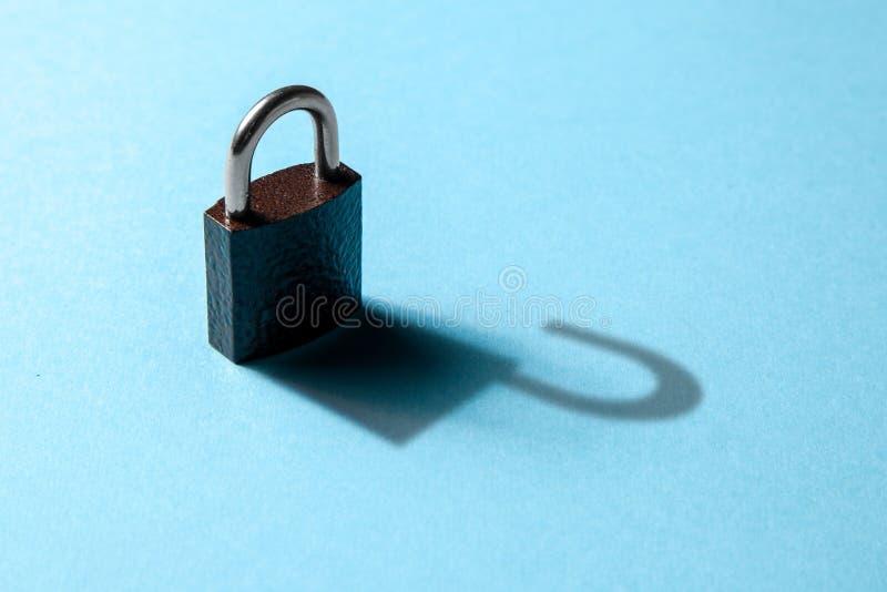 Le concept d'information privée disponible, entaillant Serrure fermée sur le fond bleu avec l'ombre d'une serrure ouverte photographie stock libre de droits