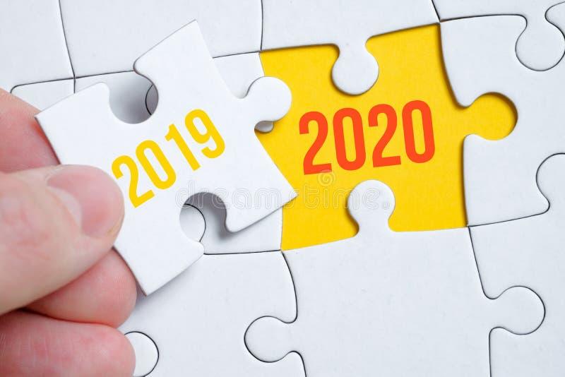Le concept de changement de l'année 2019 à 2020 Un morceau du puzzle est tenu par un homme avec ses doigts sur un fond jaune photographie stock libre de droits