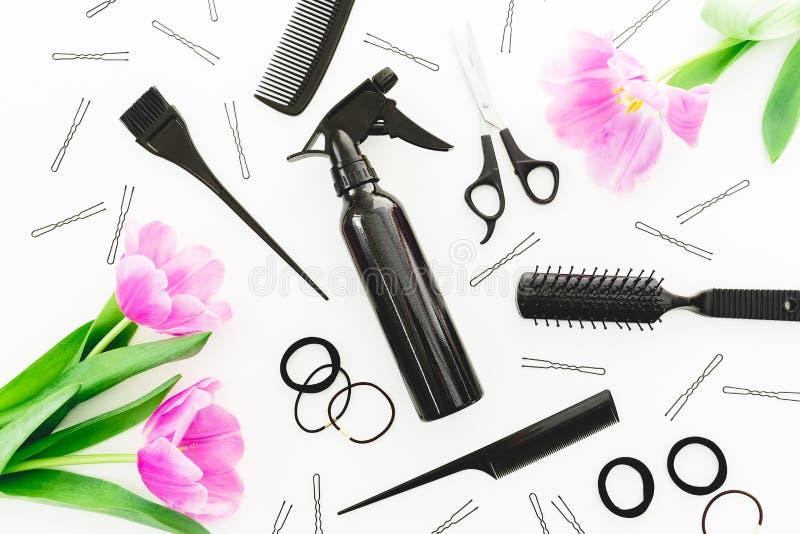 Le concept de coiffeur avec le jet, les ciseaux, les peignes, la barrette et les tulipes fleurit sur le fond blanc Configuration  images libres de droits