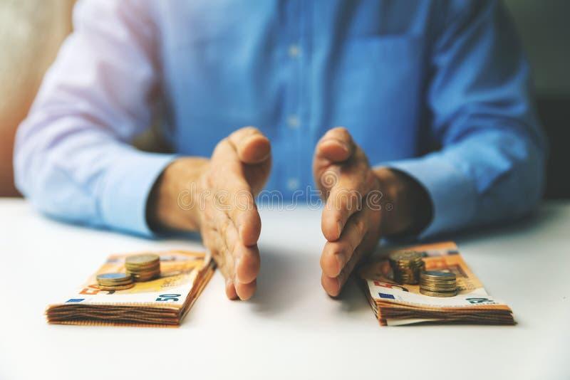 Le concept de gestion financière et de planification budgétaire - homme d'affaires divisant l'argent sur la table image stock