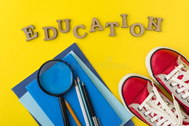 Le concept de l'éducation Espadrilles rouges, fournitures scolaires, livres, carnets avec le fond jaune photos stock