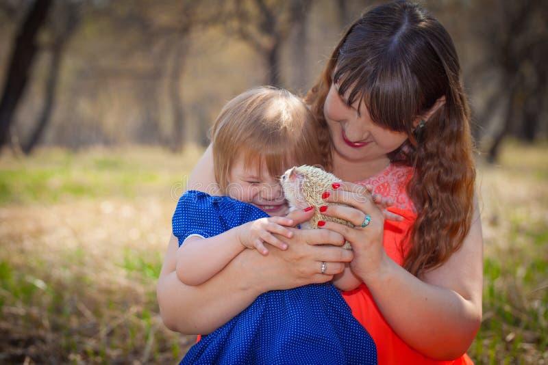 Le concept de l'amusement La maman et la fille jouent avec un h?risson photo stock
