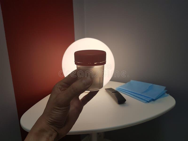 Le concept de l'essai médical du sperme, et insémination artificielle La main du docteur tient un récipient en plastique avec photo libre de droits