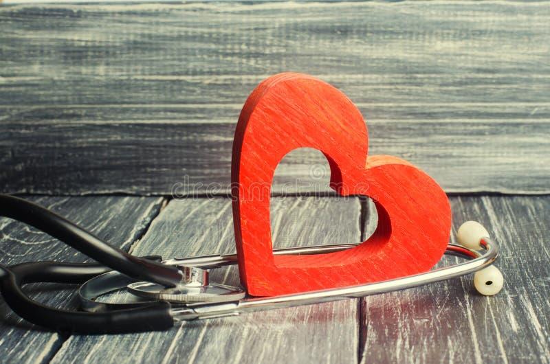 Le concept de la médecine de la famille et de l'assurance stéthoscope et coeur sur un fond en bois image stock