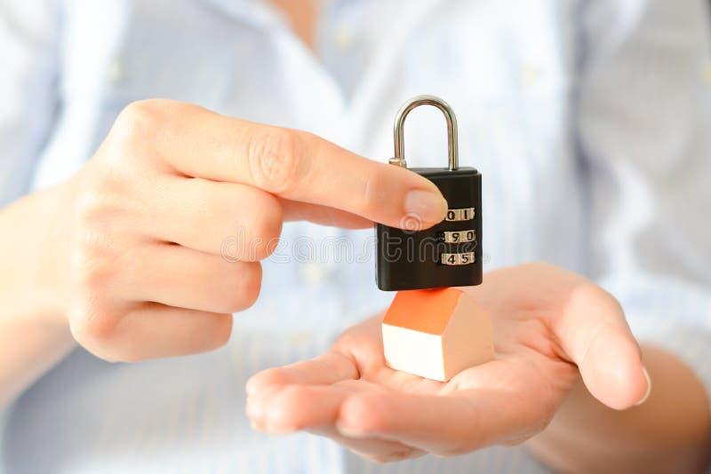 Le concept de la sécurité à la maison ou de l'assurance avec la serrure de chiffre sur le toit d'une maison miniature photographie stock libre de droits