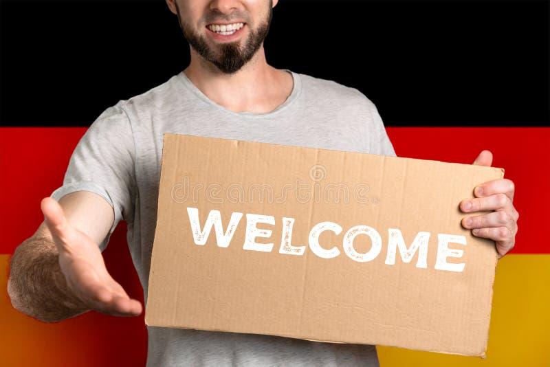Le concept de la tolérance pour des immigrés et des personnes de différentes positions de la vie Un homme tient un carton et étir photo libre de droits