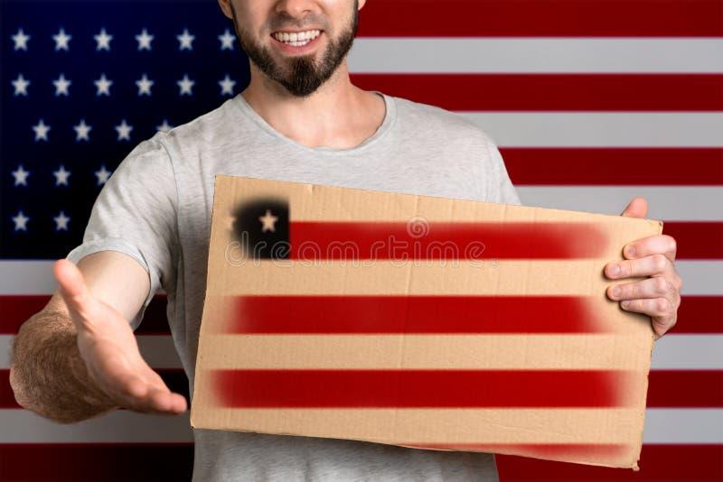 Le concept de la tolérance pour des immigrés et des personnes de différentes positions de la vie Un homme tient un carton et étir images stock