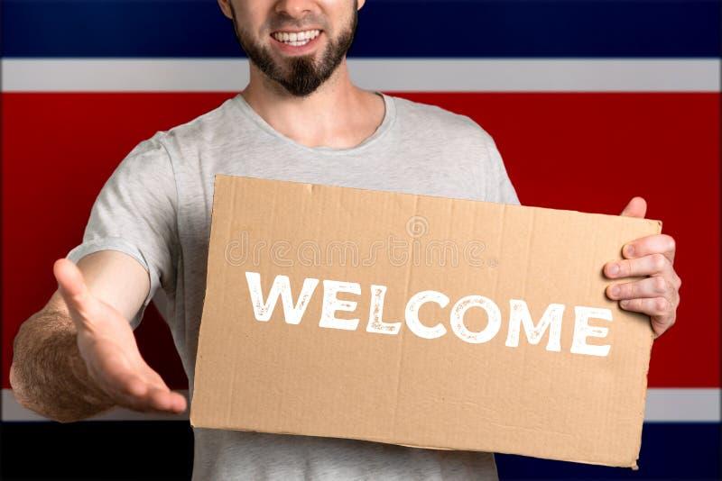 Le concept de la tolérance pour des immigrés et des personnes de différentes positions de la vie Un homme tient un carton et étir images libres de droits