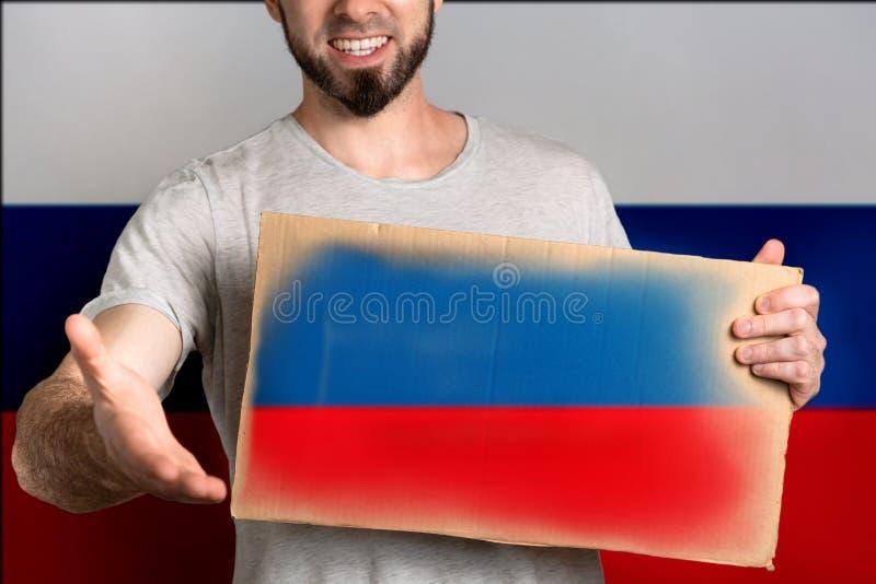 Le concept de la tolérance pour des immigrés et des personnes de différentes positions de la vie Un homme tient un carton et étir photos stock
