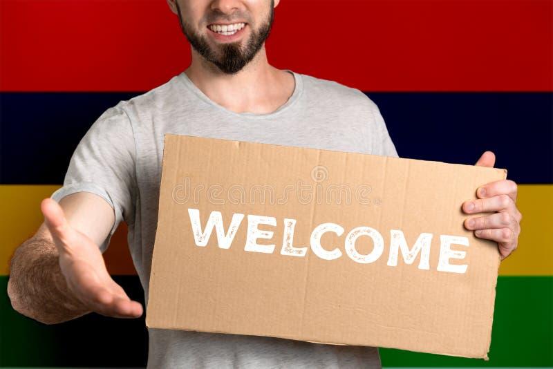 Le concept de la tolérance pour des immigrés et des personnes de différentes positions de la vie Un homme tient un carton et étir image stock