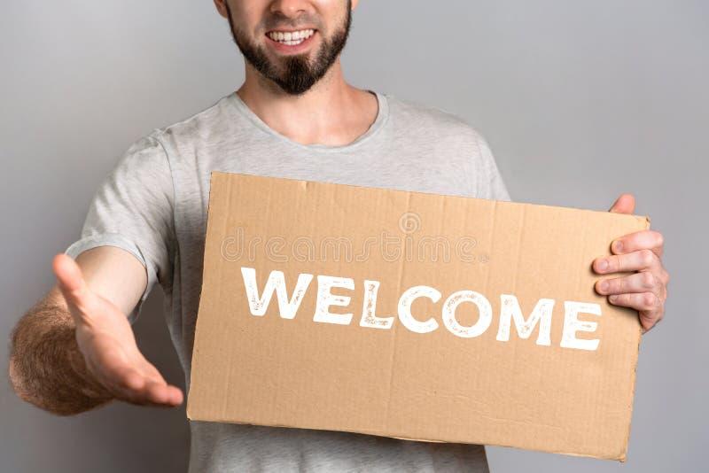 Le concept de la tolérance pour des immigrés et des personnes de différentes positions de la vie Un homme tient un carton et étir photo stock