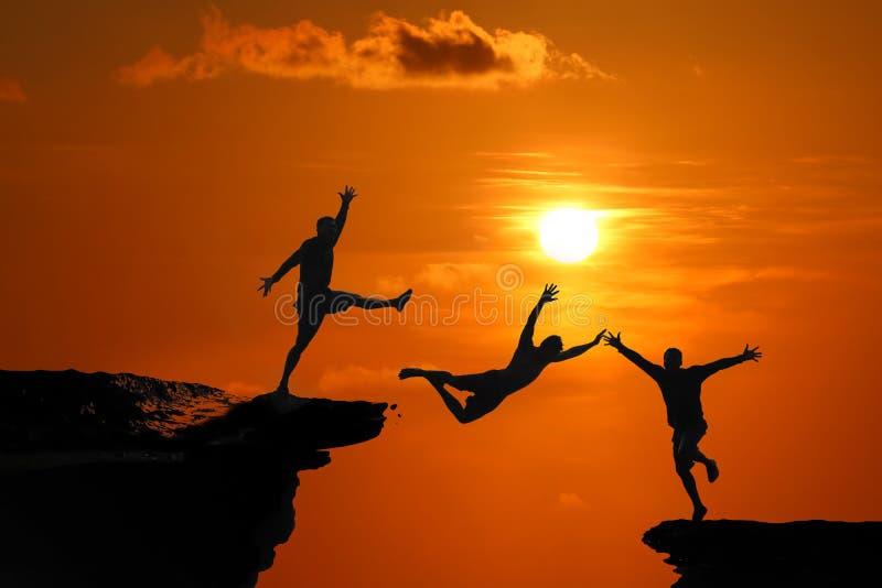 Le concept de la trahison et l'aide des amis, silhouette des hommes sont sautés entre la haute falaise à un coucher du soleil rou photo stock
