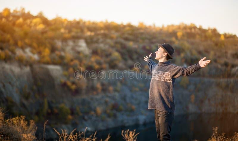Le concept de liberté Homme libre en pull et chapeau noir les bras ouverts au coucher du soleil admirez la vue sur la nature du l photo libre de droits