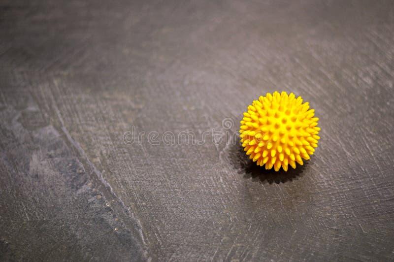 Le concept de mode de vie de santé et de sport, une boule jaune de massage avec des boutons se trouve sur le plancher gris photo libre de droits