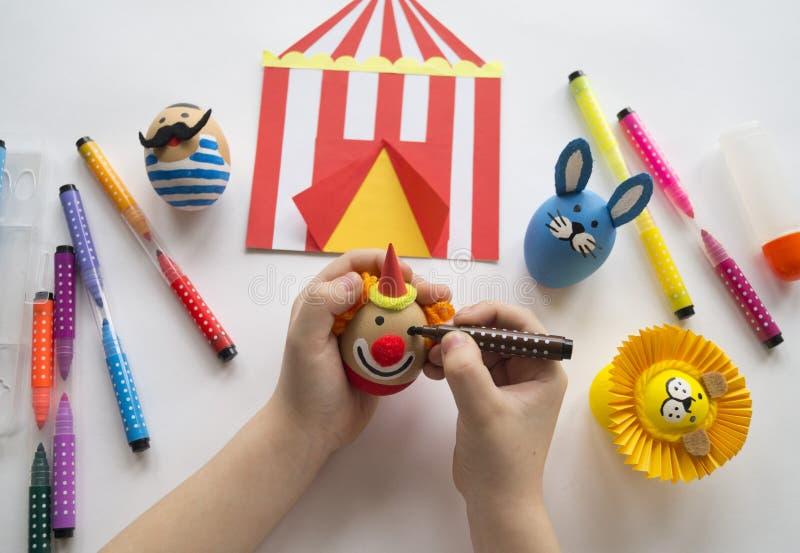 Le concept de Pâques avec des oeufs faits main mignons et gais, un lapin, un clown, un homme fort et un lion images libres de droits